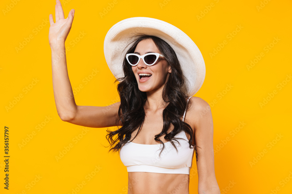 Fototapeta Image of stylish woman in swimsuit and hat smiling and waving hand
