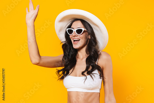Obraz Image of stylish woman in swimsuit and hat smiling and waving hand - fototapety do salonu