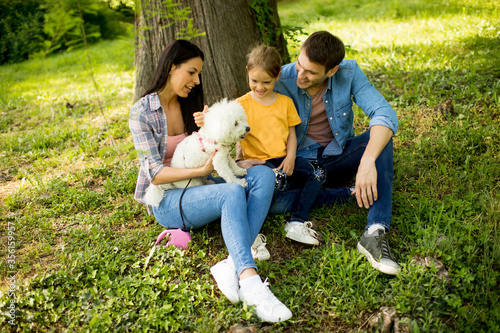Happy family with cute bichon dog in the park Wallpaper Mural
