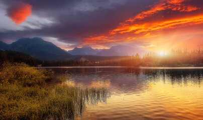 Fototapeta Vintage Beautiful Autumn Landscape. Majestic Sunset on Strbske Pleso lake. Colorful morning view of High Tatra, Slovakia, Europe. Amazing Nature background. Wonderful Picturesque Scene. Picture of wild area