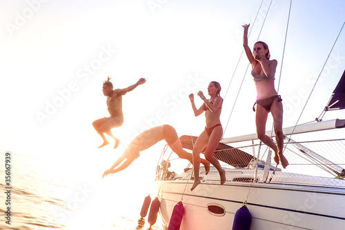Young millenial friends jumping from sailboat at sea ocean trip - Guys and girls having summer fun together at sail boat party day - Luxury excursion concept on bright vivid filter with soft focus