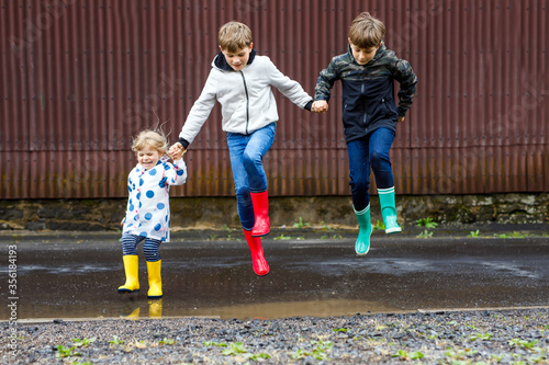 Obraz na plátně Three children, toddler girl and two kids boys wearing red, yellow and green rain boots and walking during sleet