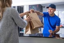 Camarero Entregando A Una Clienta Comida Para Llevar En Bolsas De Cartón En El Restaurante