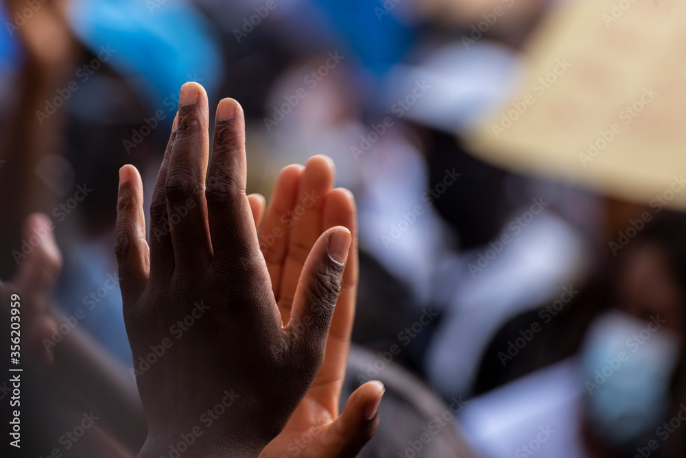 Fototapeta Colored person clapping his hands in the middle of a protest against racism, unfocused background