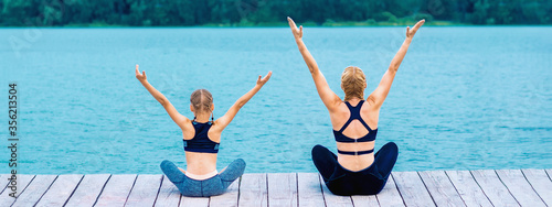 Mother and daughter doing yoga at the shore of the lake in summer Принти на полотні