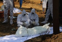Relative Who Wearing Personal Protection Kit Mourn Next Of A Man Who Died Form The Coronavirus Disease COVID-19 Before Lowering His  Body Into A Graveyard At The Burial Designated Spot For COVID-19 At