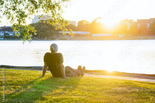 Back view gray hair mature man sitting on the green grass at the bank of park's lake and enjoying the sunset Canvas Print