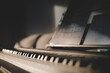 Low shot of 88 keys of a keyboard and sheet music. Close up with light from side