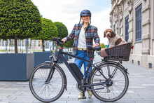 Young Woman Pushing Her E-bike With The Dog In The Basket