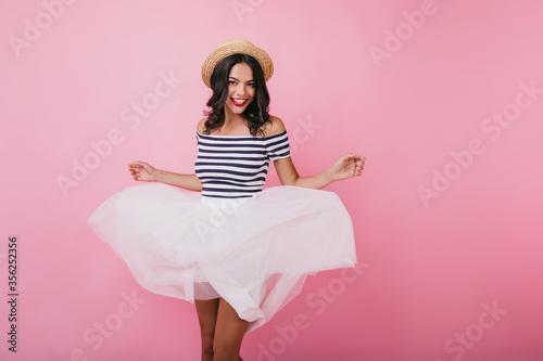 Fototapeta Tanned romantic lady playfully posing on pink background
