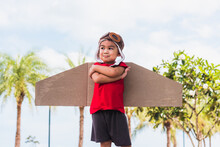 Happy Asian Funny Child Or Kid Little Boy Smile Wear Pilot Hat And Goggles Play Toy Cardboard Airplane Wing Fly Stand Crossed Arm Against Summer Sky Cloud On Garden Background, Startup Freedom Concept