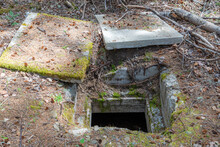 The Entrance To An Old Underground Concrete Bunker. The Entrance Is Open With Two Concrete Covers On The Ground. Situated In The Woods.