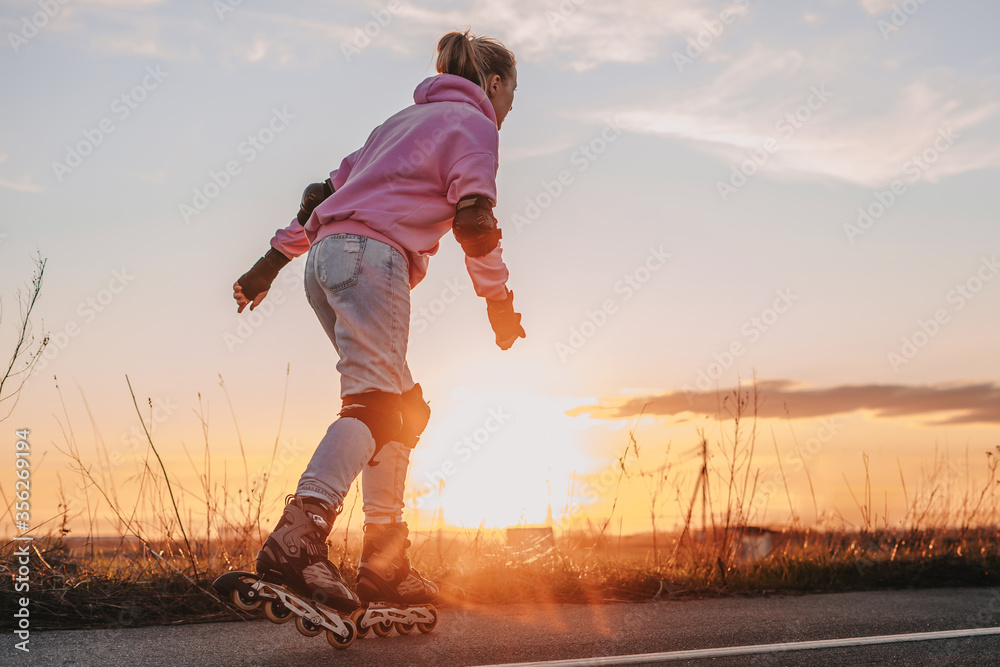 Fototapeta young girl rides roller skates on the road against the background of the sunset