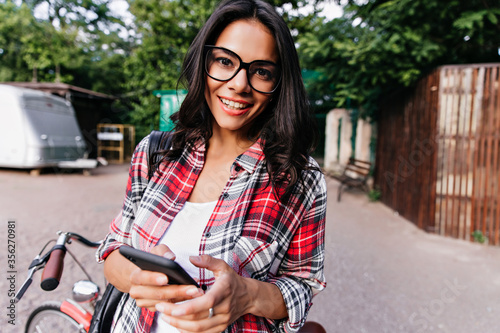 Obraz na plátne Curious brunette girl with phone in hand looking to camera