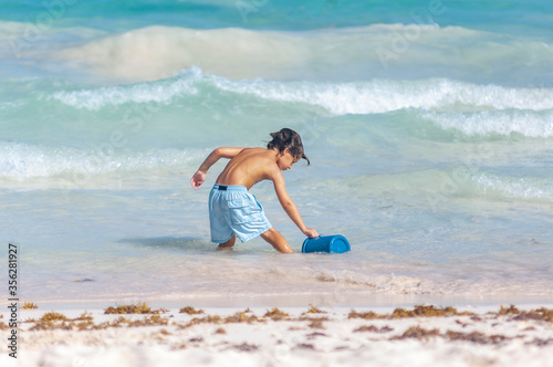 Slika na platnu Niño en traje de baño azul llena balde azul de agua en playa del Caribe