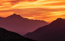 Fiery Skies Over Desert Mounta...