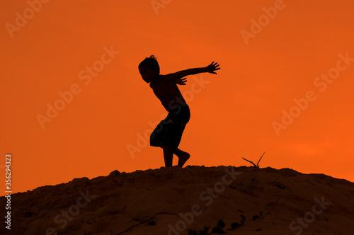 Silueta de niño a punto de saltar desde duna de playa con atardecer naranja en vacaciones de verano Wallpaper Mural