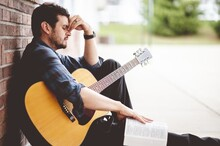 Sad Man Sitting On The Ground Holding A Book And A Guitar