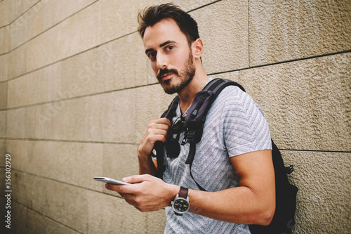 Fotografija cheerful man wanderer use cell telephone while standing against street wall wit