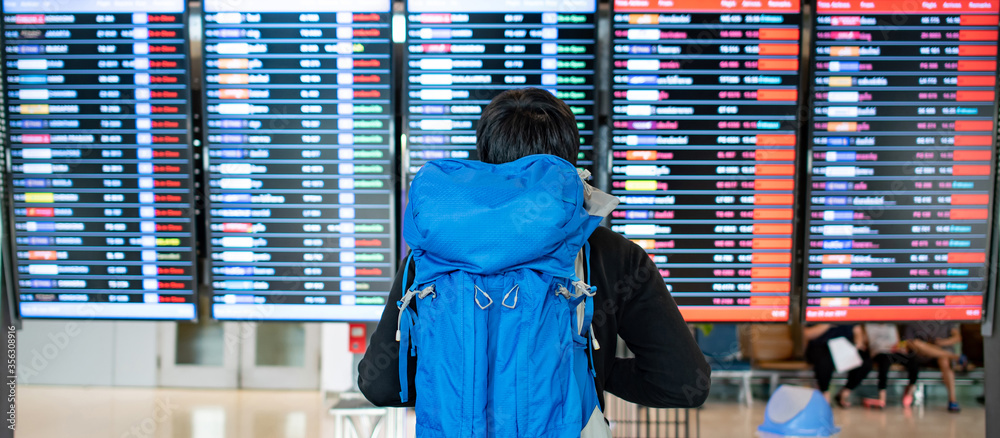 Fototapeta Vacation travel concept. Asian man backpacker and tourist carrying blue backpack checking flight information schedule on arrival departure board in international airport terminal.