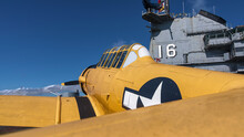 Yellow T 6 Texan Training Prop Plane On WW2 Era Lexington Aircraft Carrier Flight Deck In Texas With Control Tower In Background.