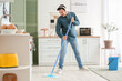 Handsome young man mopping floor in kitchen