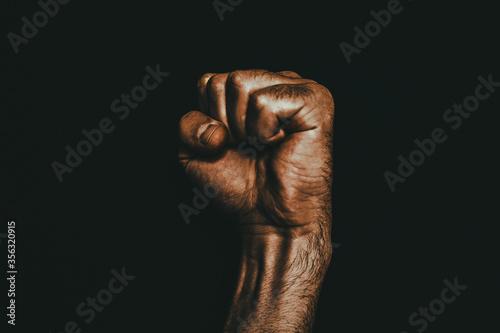 Photo Male black fist on a black background