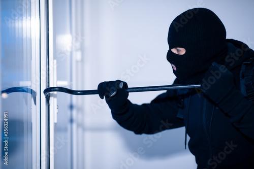 Carta da parati Robber in black balaclava cracking door with crowbar