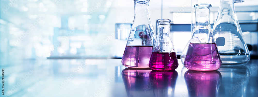 Fototapeta purple glass flask in blue research chemistry science banner laboratory background