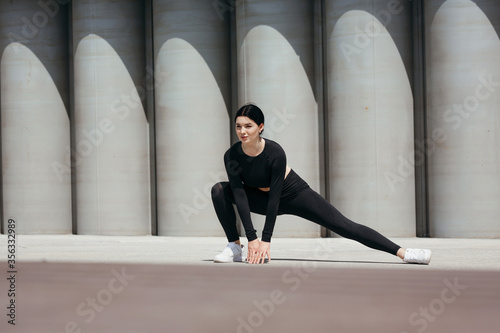 Fototapeta Street workout of a beautiful asian girl lunging for stretching inner thigh musc