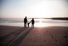 海辺で夕日を手を繋ぎ...