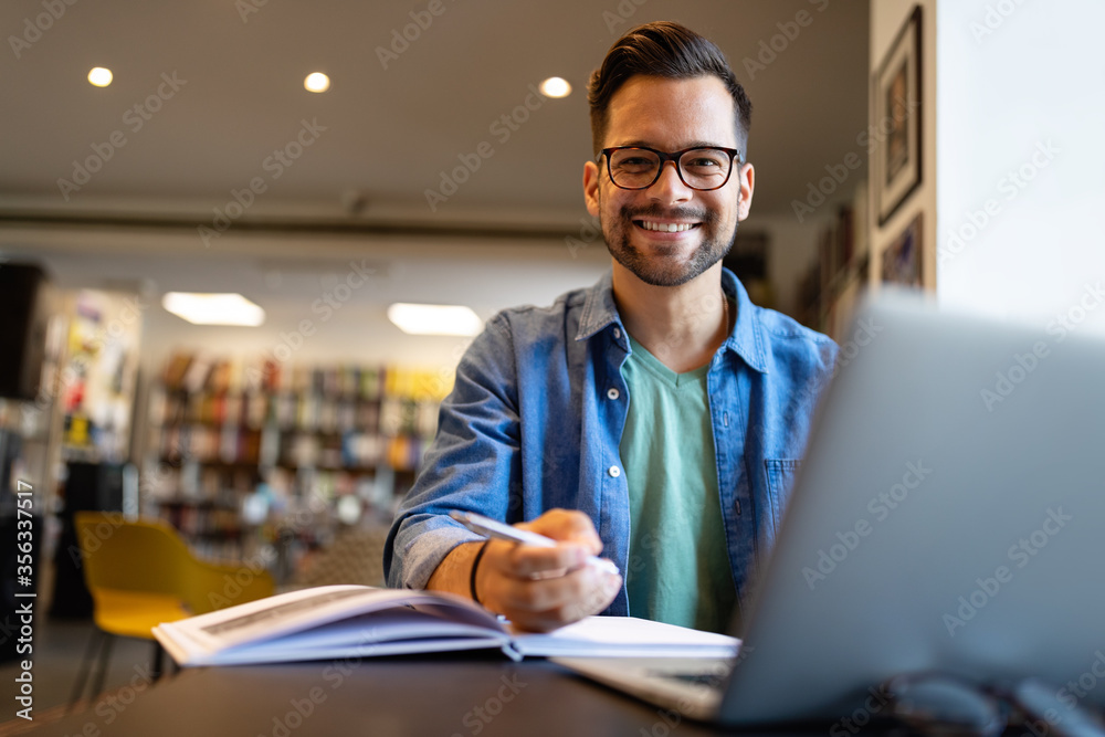 Fototapeta Smiling male student working and studying in a library