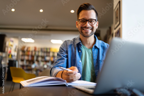 Fototapeta Smiling male student working and studying in a library obraz