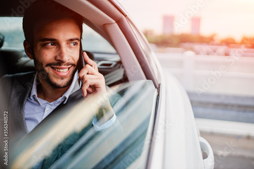 Fotografering Businessman talking on a phone and looking through the window from the car