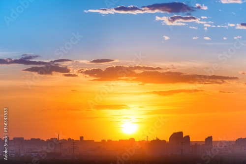 Fototapeta Sunset in big city, landscape with dramatic sky, clouds and sun rays obraz