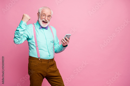 Fototapeta Delighted crazy pensioner use smartphone celebrate social network lottery victory raise fists scream yes wear teal turquoise brown pants purple bow tie isolated pastel pink color background obraz