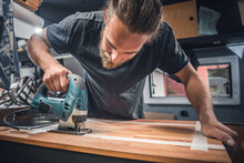 Man Working On The Countertop Inside A Camper Van