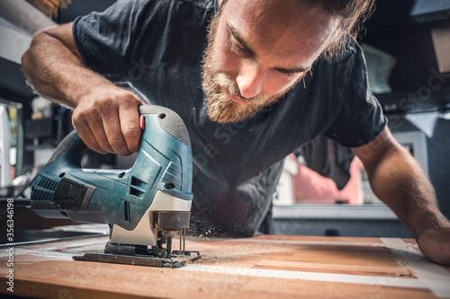 Photo Man using a jigsaw on a wooden countertop
