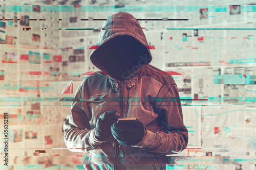Fotografija Hooded hacker person using smartphone in infodemic concept