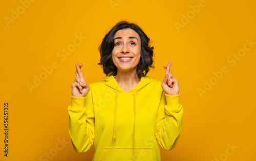 Photo Things are going right! Close-up photo of excited beautiful girl dressed in a yellow hoodie, smiling and crossing her fingers, waiting for some lucky result while things are going right for her
