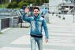 Positive man in earphones waving hand at camera on urban street