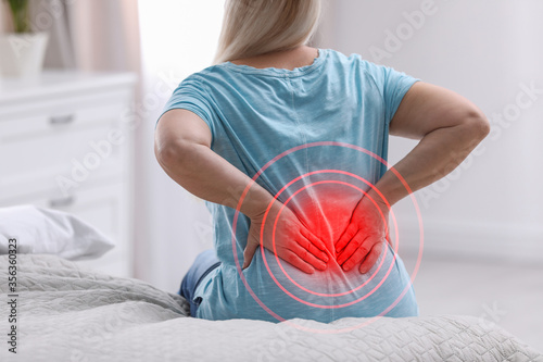 Obraz Senior woman suffering from back pain after sleeping on uncomfortable mattress at home, closeup - fototapety do salonu
