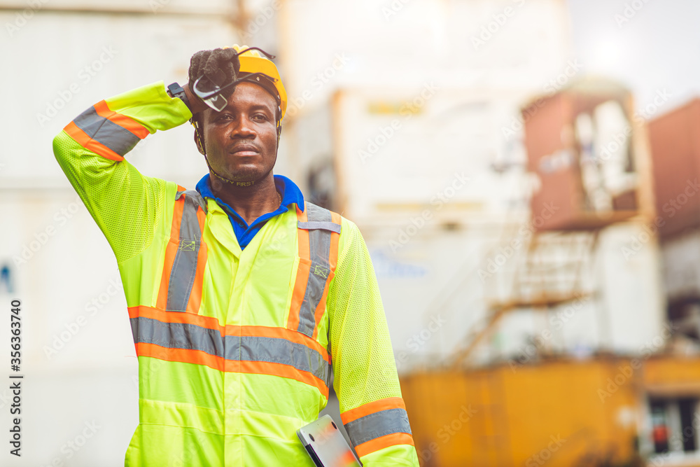Fototapeta Tired stress worker sweat from hot weather in summer working in port goods cargo shipping logistic ground,  Black African race people.