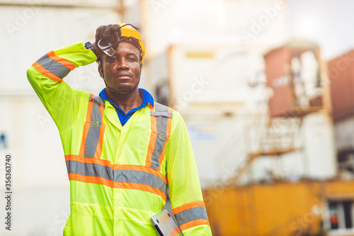 Fotomural Tired stress worker sweat from hot weather in summer working in port goods cargo shipping logistic ground,  Black African race people