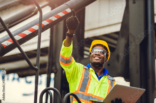 Fotografía Black African American worker as staff foreman proud to happy smile working control loading cargo in shipping logistic warehouse with safety suit