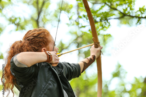 Sporty young woman practicing archery outdoors Canvas Print