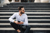 Fototapeta Fototapety na drzwi - Young attractive bearded businessman sitting on stairs in front of his company, holding smart phone and listening music.