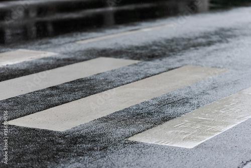Fotografia, Obraz High angle detail view of pedestrian zebra crossing on wet street tarmac on rain