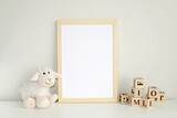 Wooden frame mock up for photo, print art, text or lettering, with nursery  toys. Blank frame on white table.