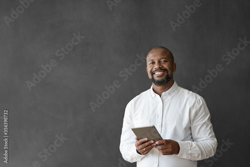 Smiling African American businessman using a tablet by a chalkboard Canvas Print